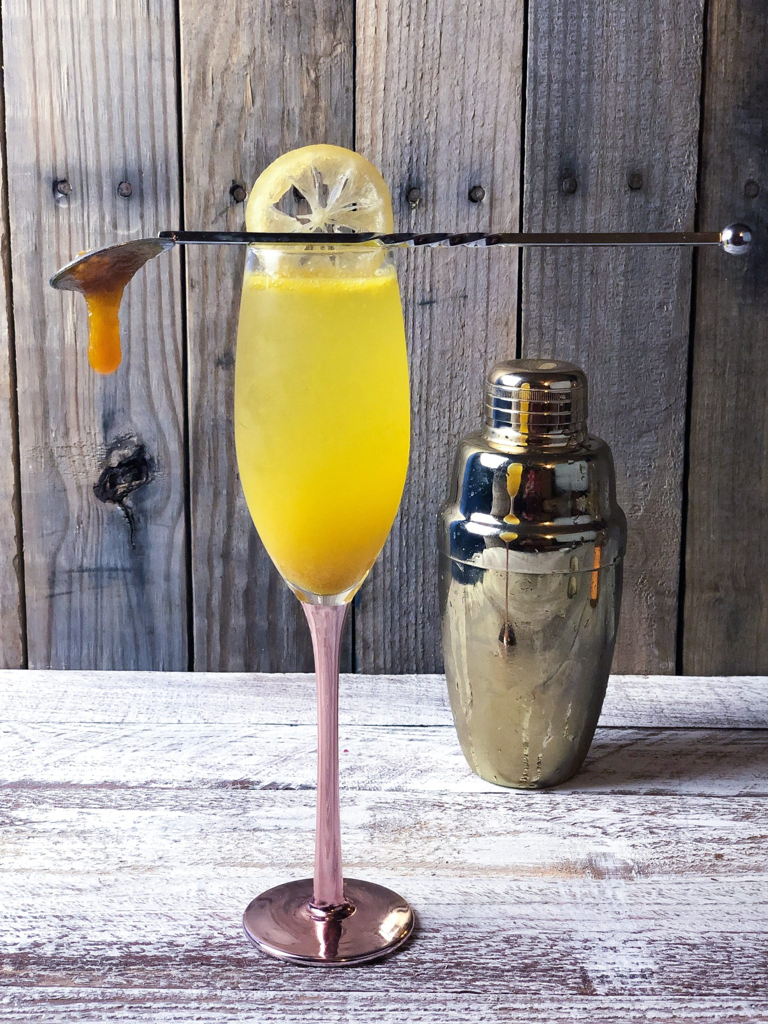 bright yellow cocktail in a champaign glass with a spoon and a dollop of jam