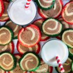 Red and green and chocolate cookies and milk with red and white straws
