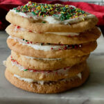 A stack of frosted sugar cookies with sprinkles.