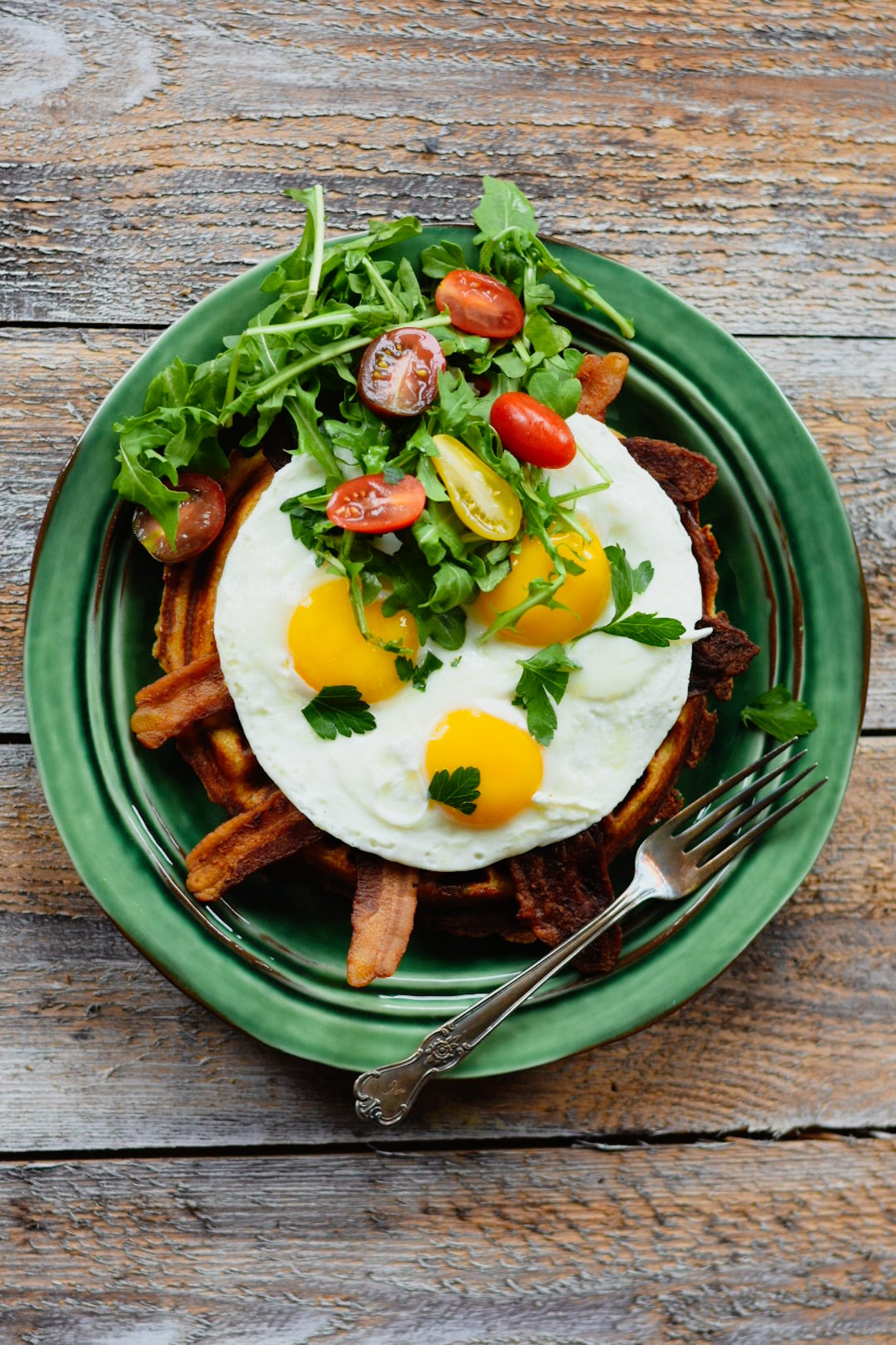 Waffle, bacon, eggs, tomato and arugula on a green plate