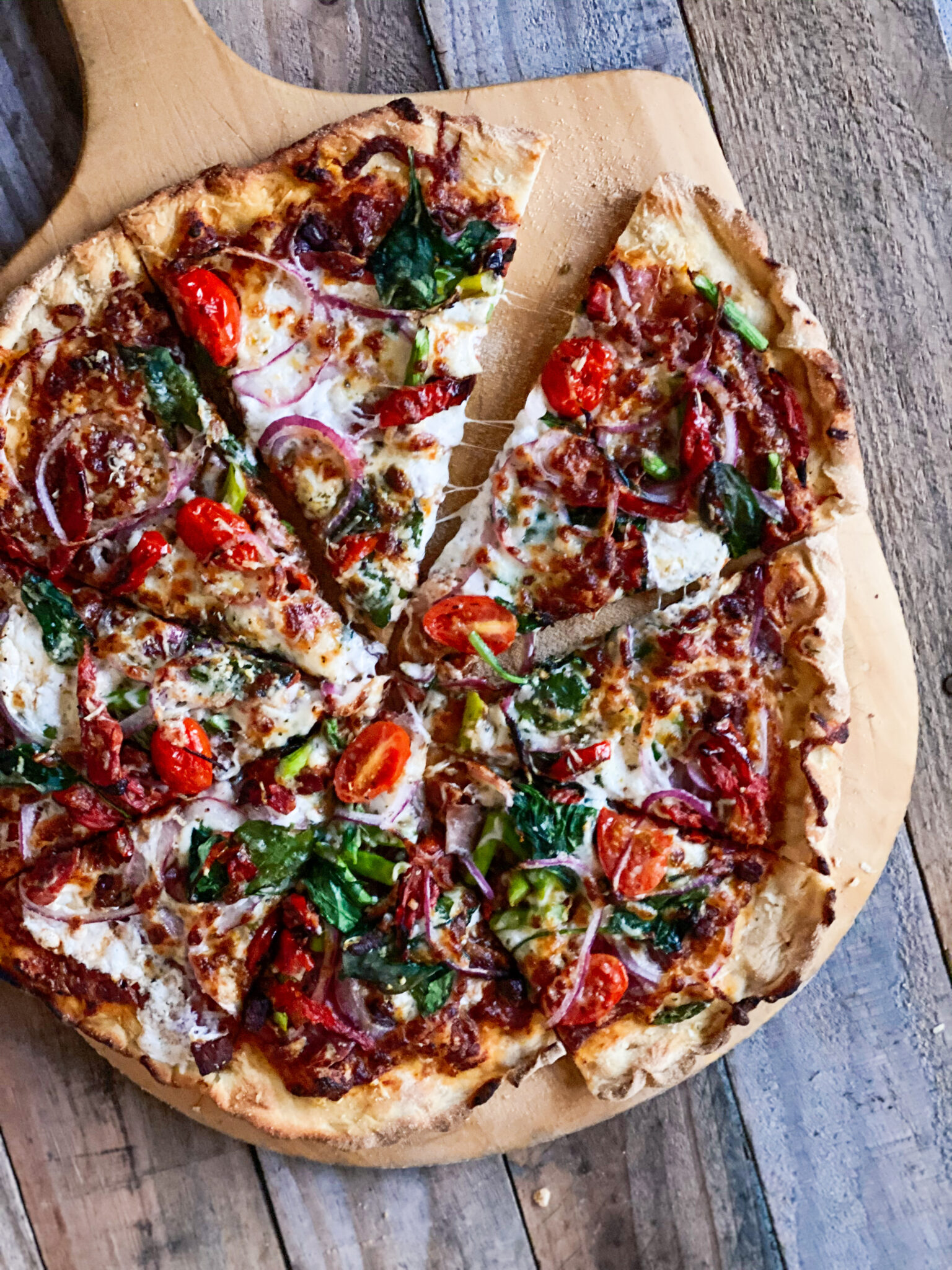 Sourdough Pizza with lots of toppings sliced on a board