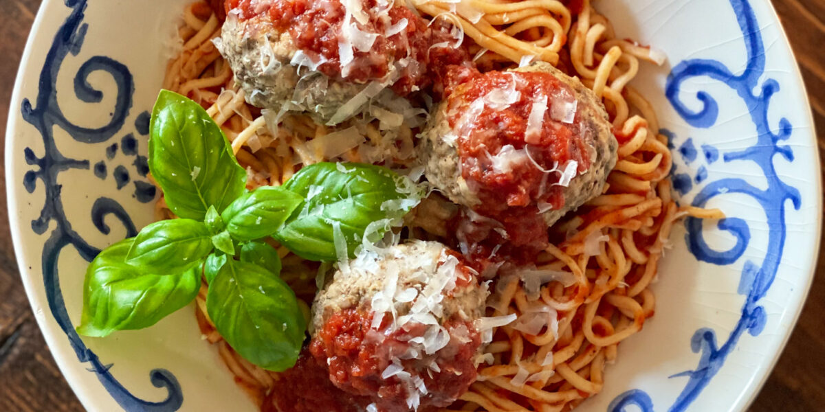 3 MEATBALLS on spaghetti and sauce in a blue and white bowl with basil