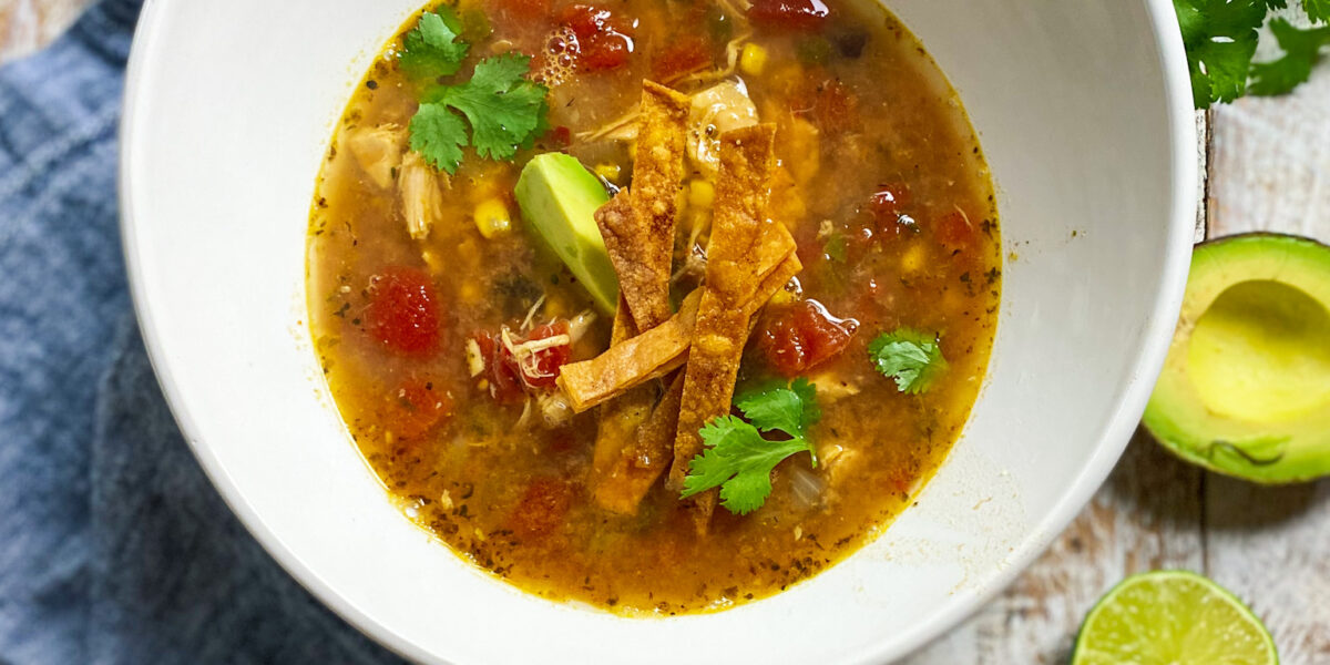 bowl of tortilla soup with avocado and lime