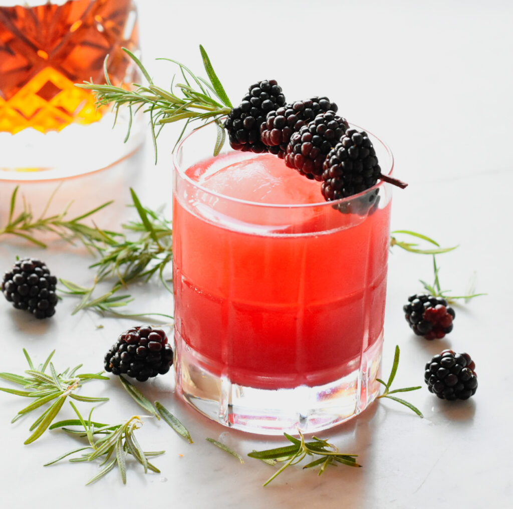 Blackberry and rosemary garnished Bourbon sour with bourbon