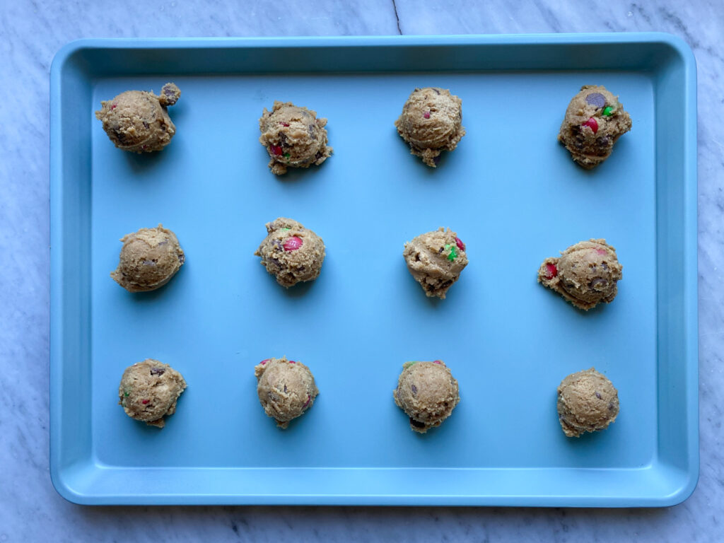 Chocolate chip M&M cookie dough on a blue cookie pan