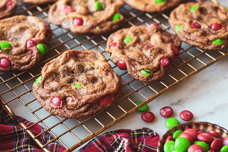M&Ms in a bowl, plaid napkin, red and white ornament and chocolate chip cookies