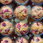 cranberry orange muffins in a muffin pan with orange glaze