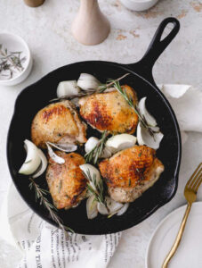 Valentines Day Dinner of Chicken thighs in a cast iron skillet with rosemary