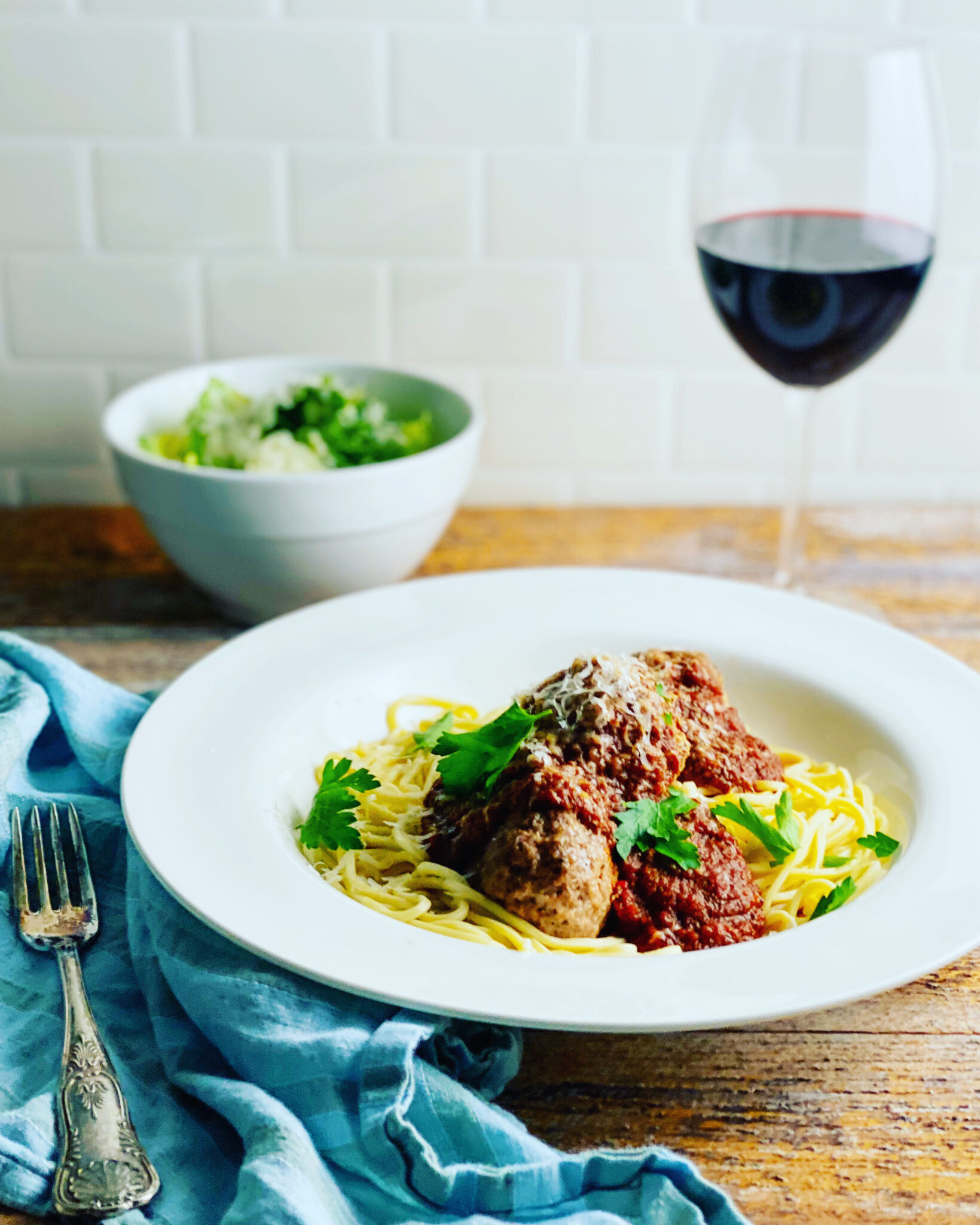 Tomato sauce and meatballs on pasta with a salad and a glass of red wine