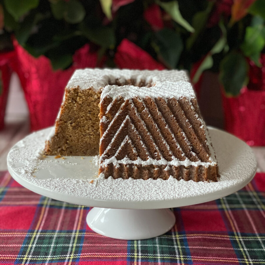 Butter Pecan Bourbon Pound Cake covered with powder sugar on a white cake stand on a plaid placemat with red flowers in background