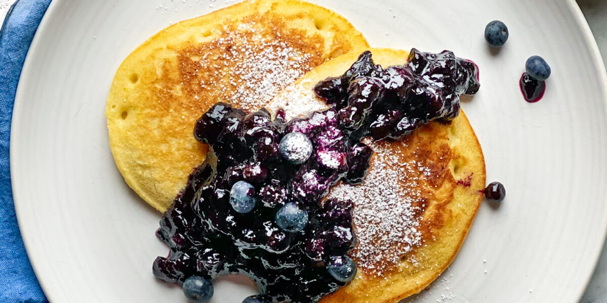2 lemon pancakes on a plate with blueberry compote and a sliced lemon and blueberries
