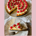 Raspberry swirl cheesecake with whipped cream and raspberries and a slice cut out on a white plate with a fork.