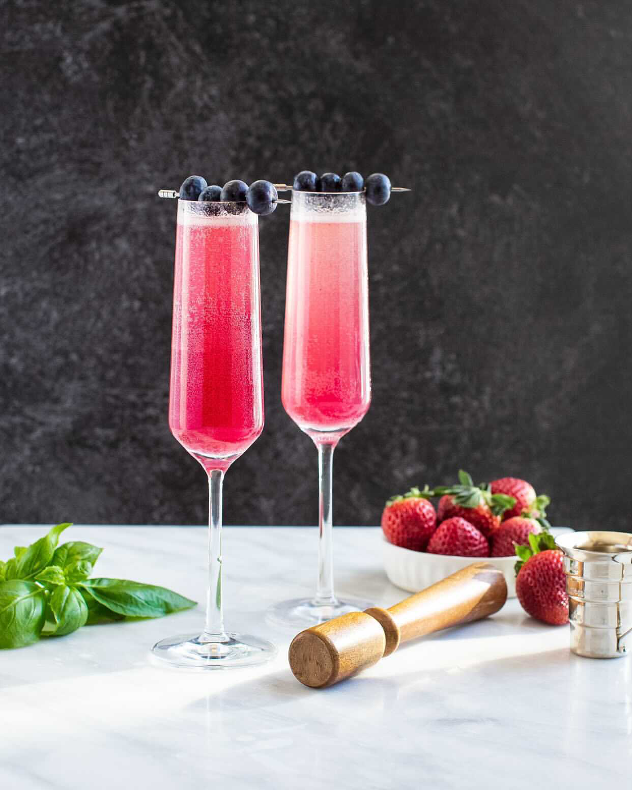 2 blueberry basil french 75 cocktails with a bowl of strawberries