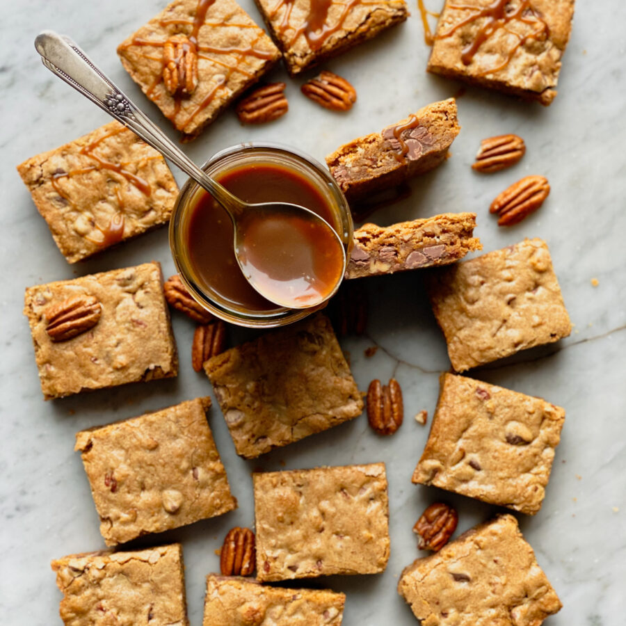 Bourbon Pecan Chocolate chip blondies and pecans on marble with salted caramel in a jar