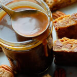 A small mason jar with bourbon salted caramel sauce and blondies