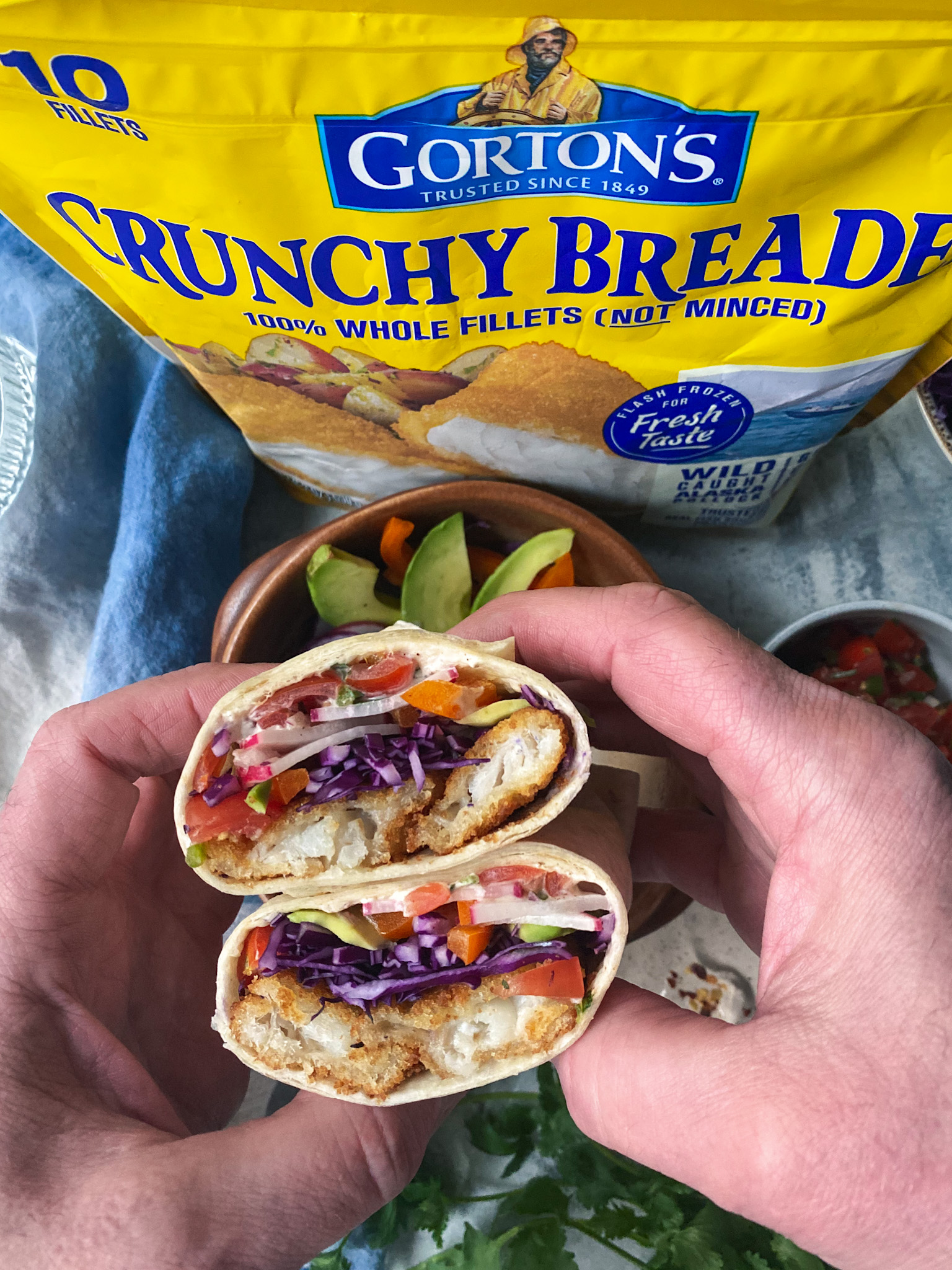 Hands holding a Baja fish burrito and a bag of Gorton's Crunchy breaded Fish