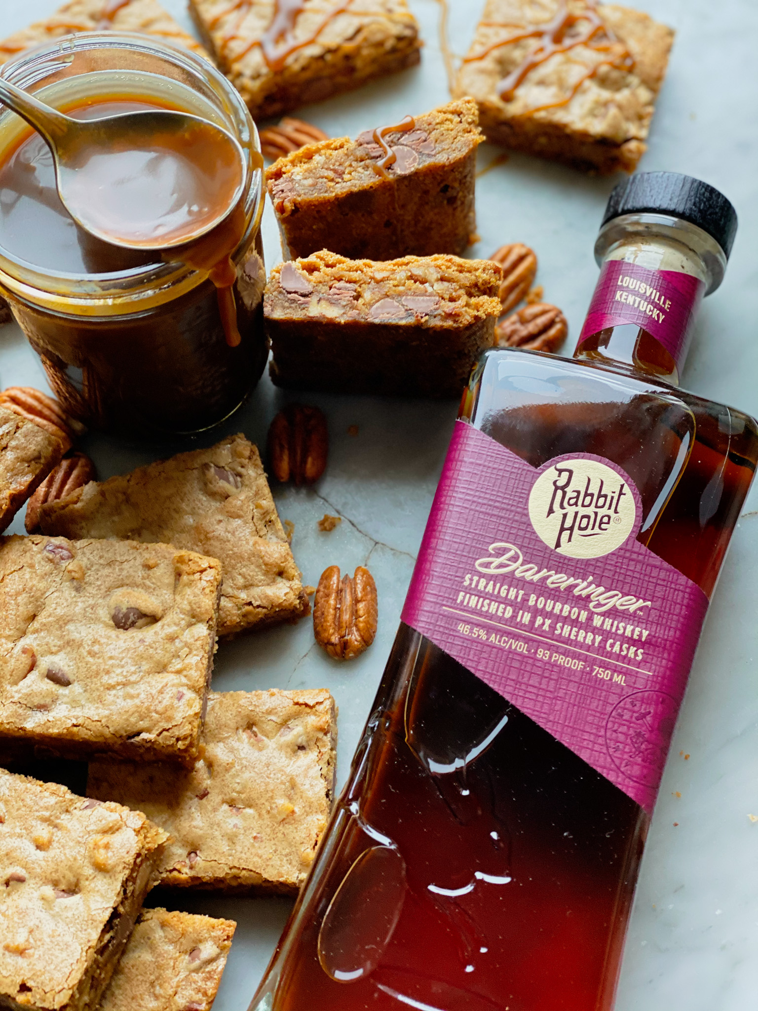 Bourbon pecan chocolate chip blondies and a bottle of rabbit hole bourbon and salted caramel blondies