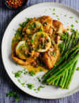 Lemon and caper white wine sauce over chicken with asparagus and hot pepper flakes