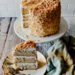 3 layer coconut cream cake with toasted coconut and a slice on a plate with a fork and a green nampkin
