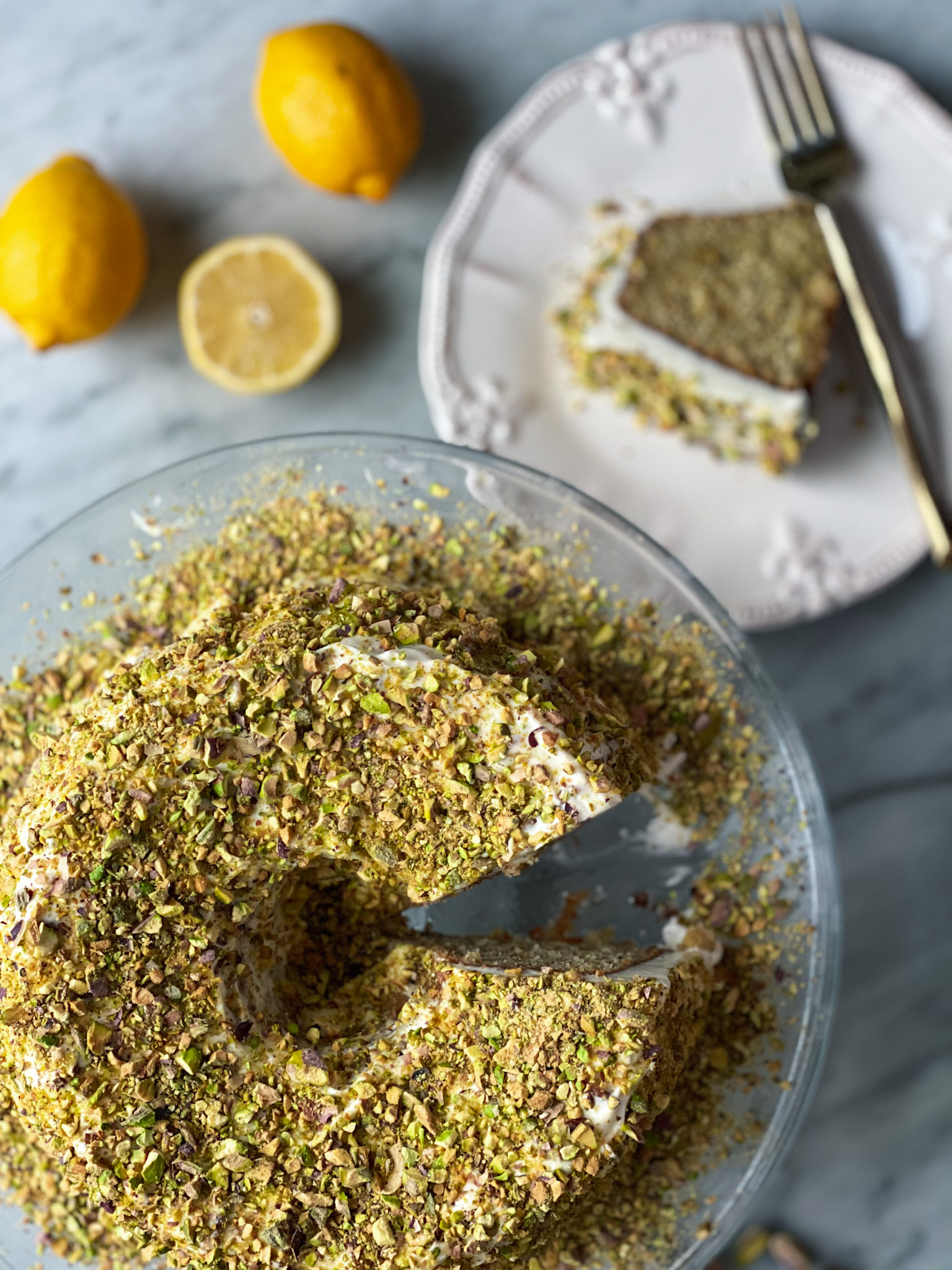 Lemon bundt cake with a slice of cake and some lemons