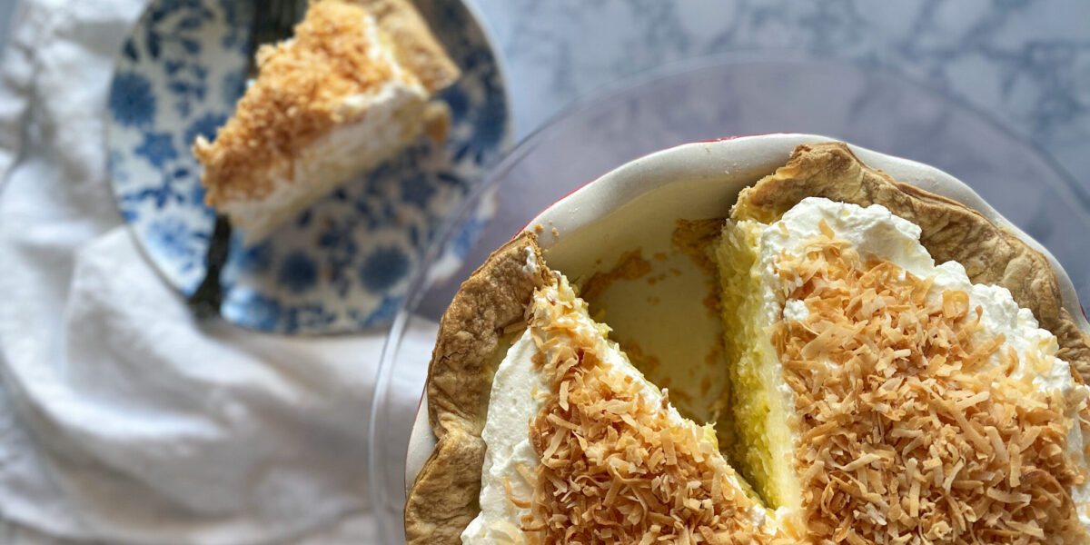 Coconut cream pie with a slice out of it on a plate