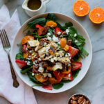 Spinach salad with oranges, strawberries, chicken, pecans, and feta, with a bowl of strawberries and pecans and an orange and a pitcher of poppyseed dressing