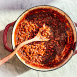 Baked beans in a cast iron dutch oven with a wooden spoon