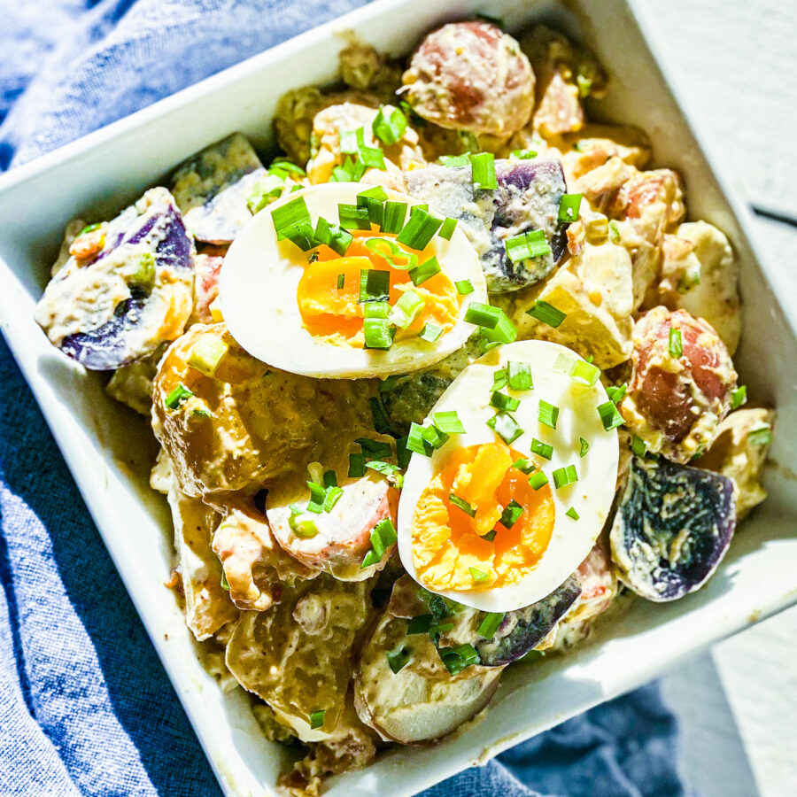 potato salad in a square bowl with eggs on top
