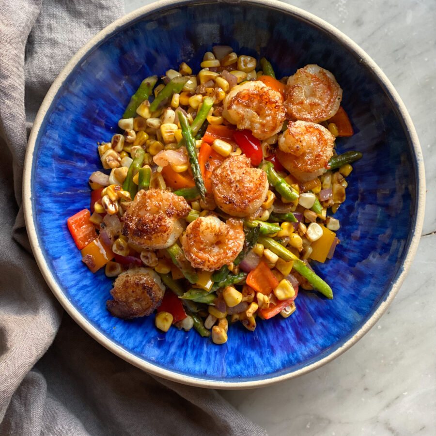 shrimp power bowl in a blue bowl with veggies and shrimp