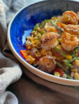 Shrimp power bowl with corn and asparagus and pepper and onions in a blue bowl