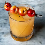 Summer Sea Breeze drink in a crystal glass with 4 cherries as a garnish.
