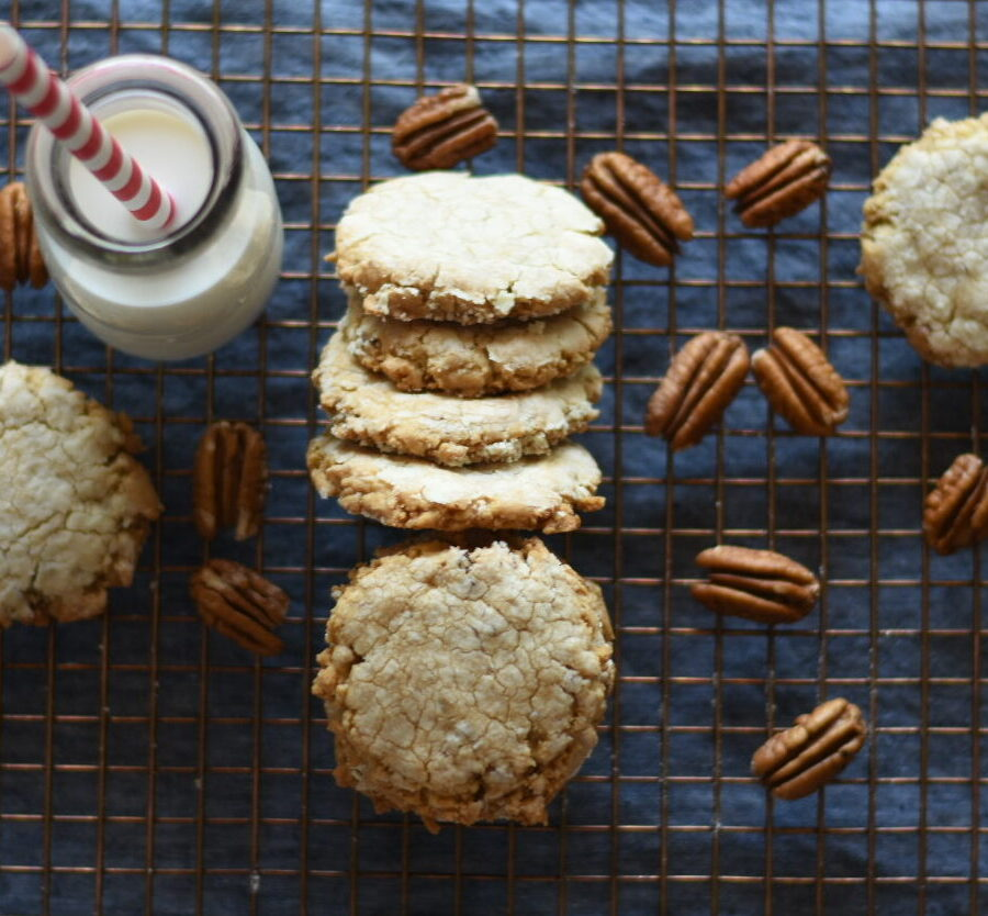 Pecan sandies and pecans and a milk glass with a red and white straw