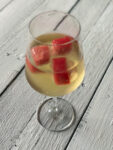 Watermelon ice cubes in a glass of wine