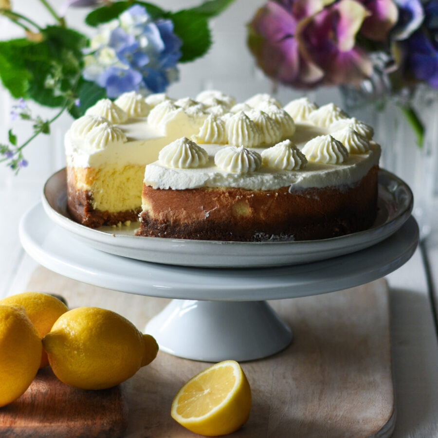 lemon cheese cake with a slice out of it and lemons and flowers