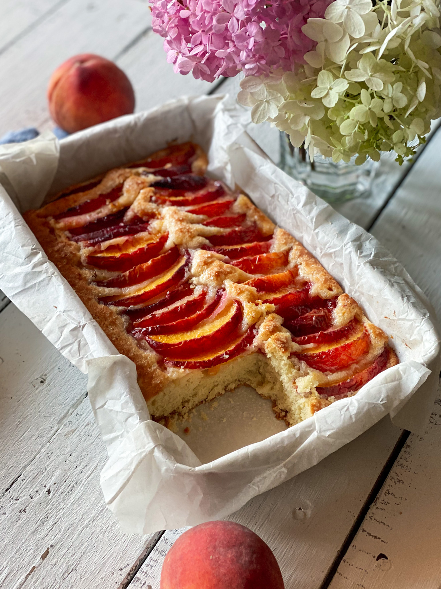 Peach topped cake with a slice out and peaches and flowers nearby