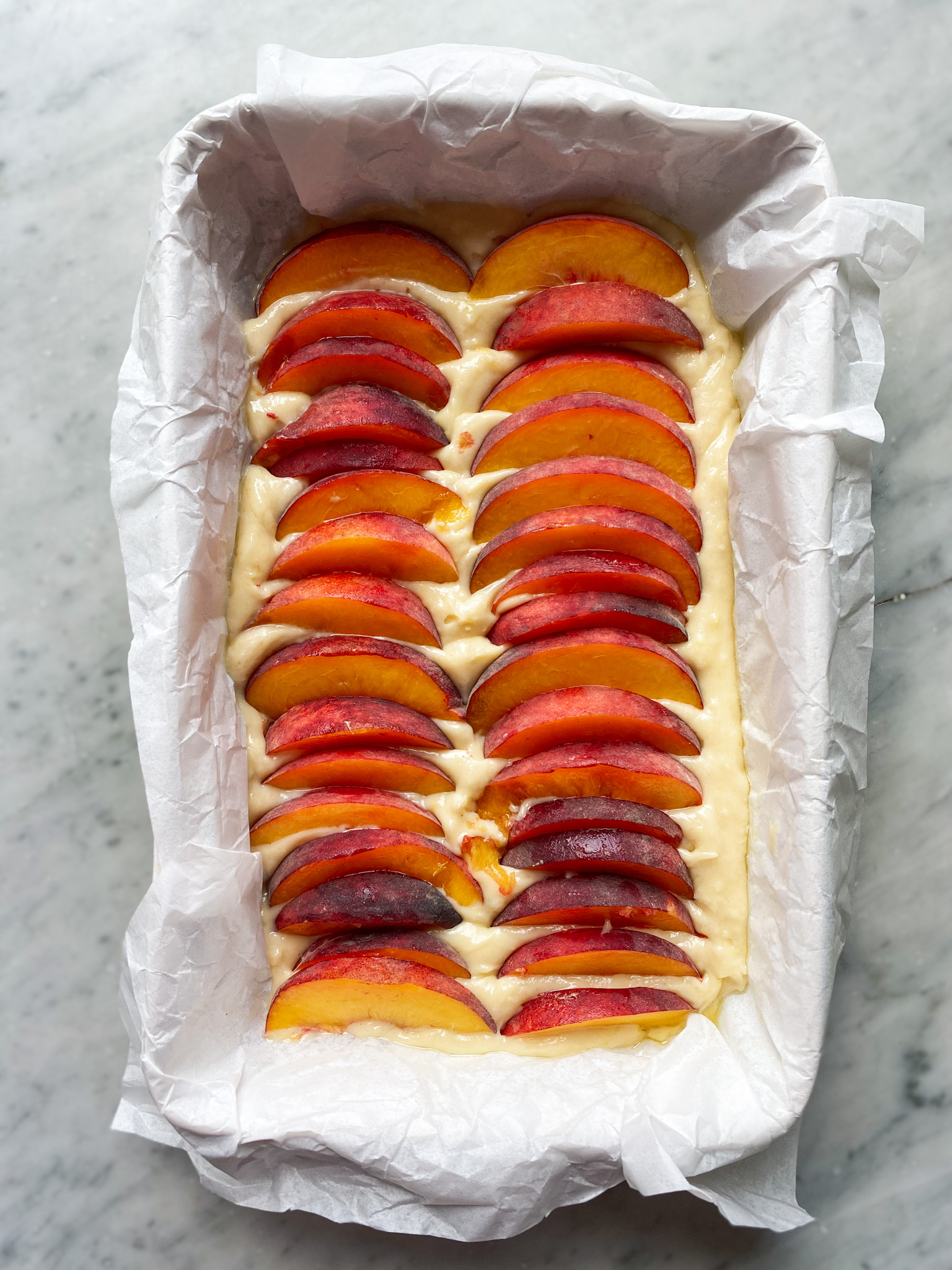cake batter in parchment in a pan with sliced peaches on top