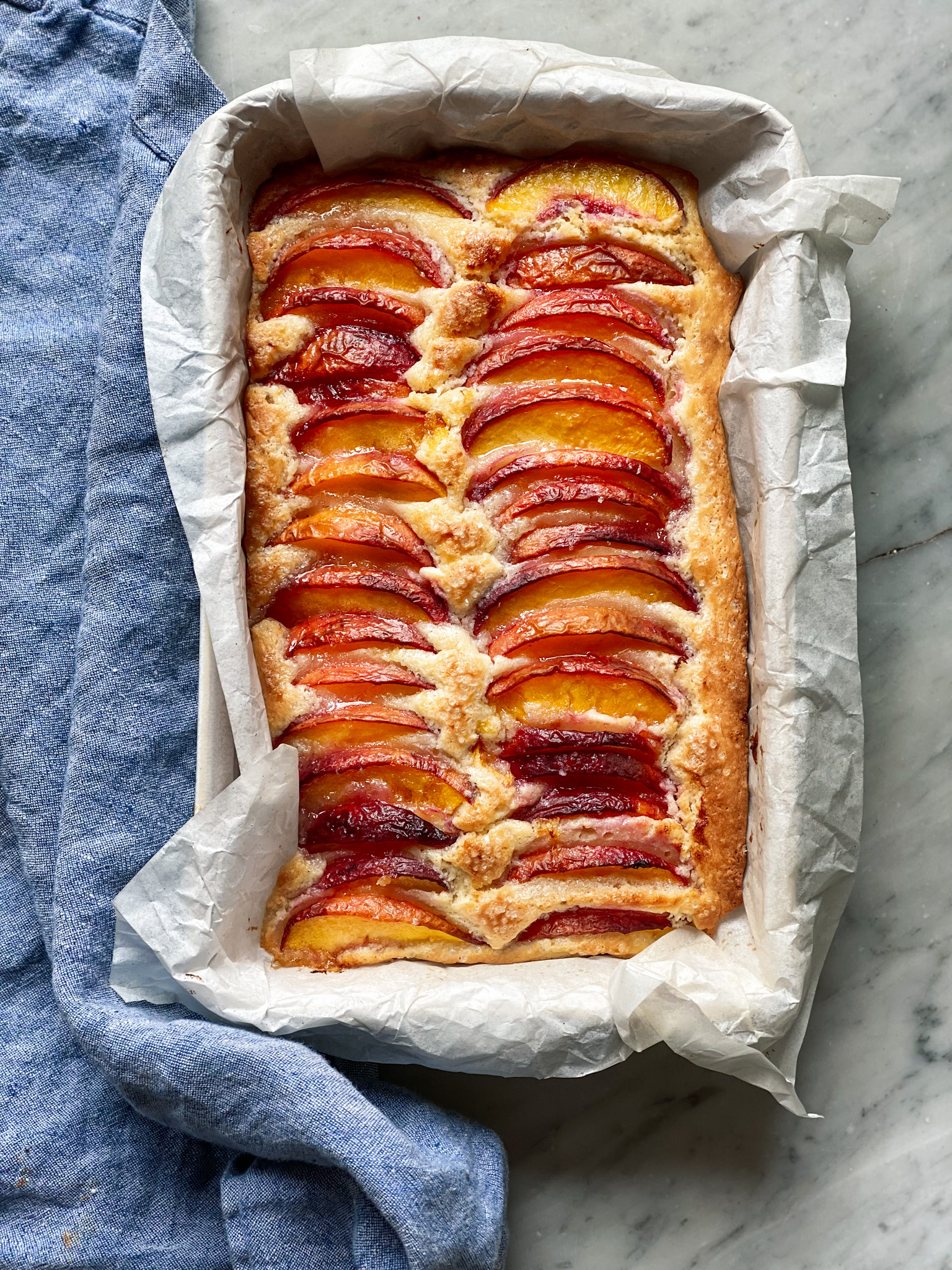 Peach topped cake in parchment with a blue napkin