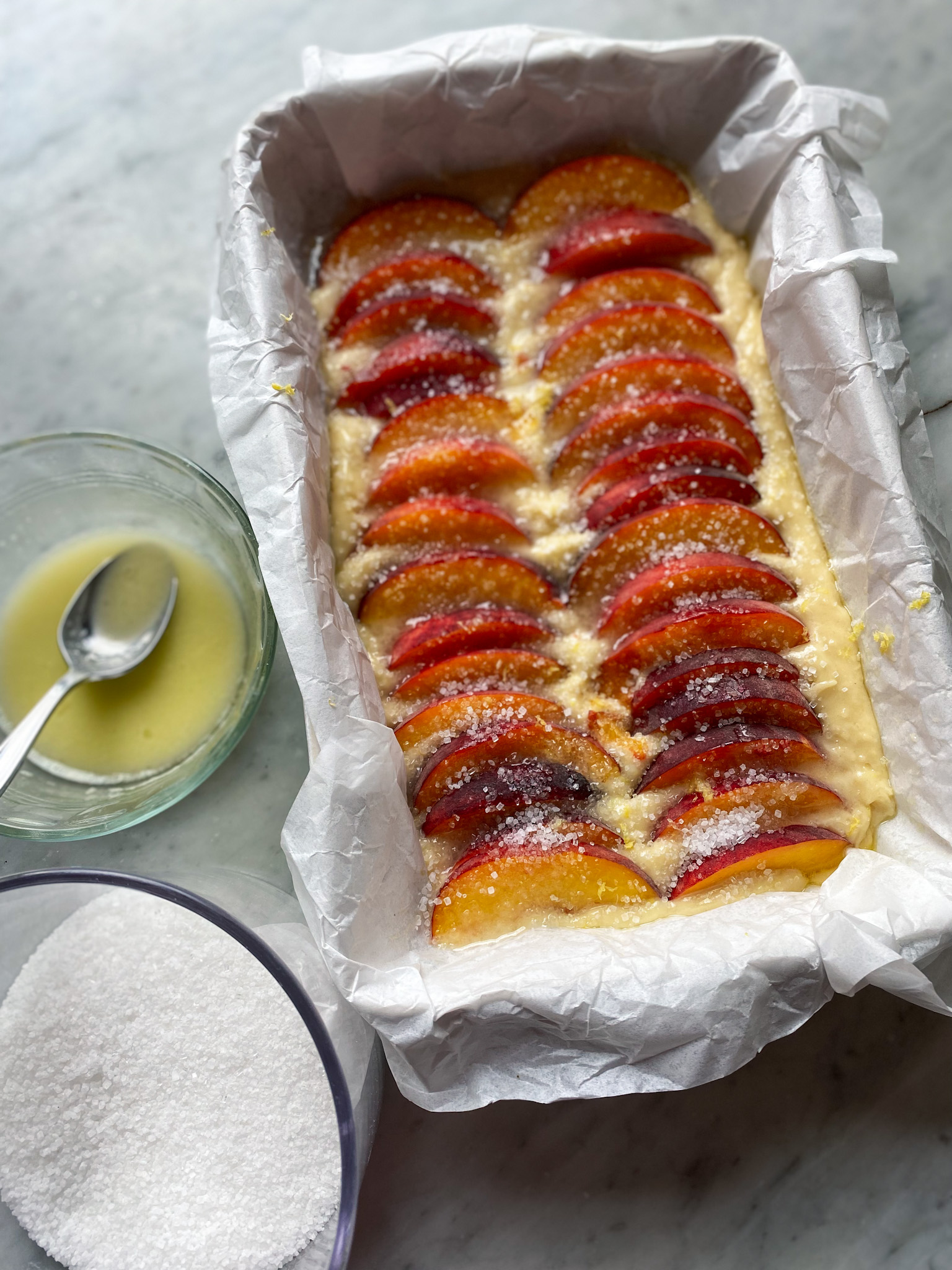 cake batter with sliced peaches on top with lemon and butter and sugar on top