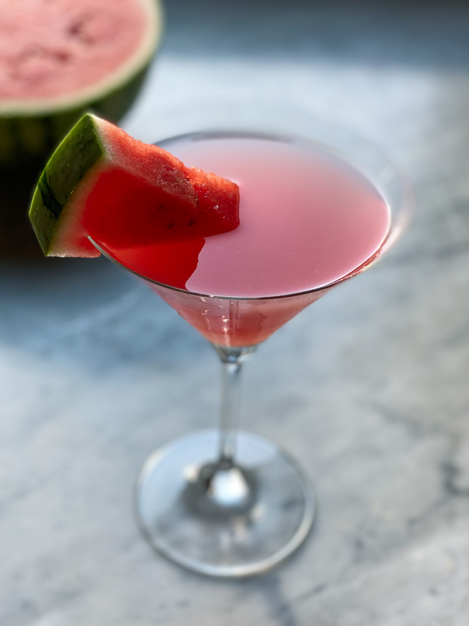 watermelon martini with a watermelon wedge and a watermelon in background