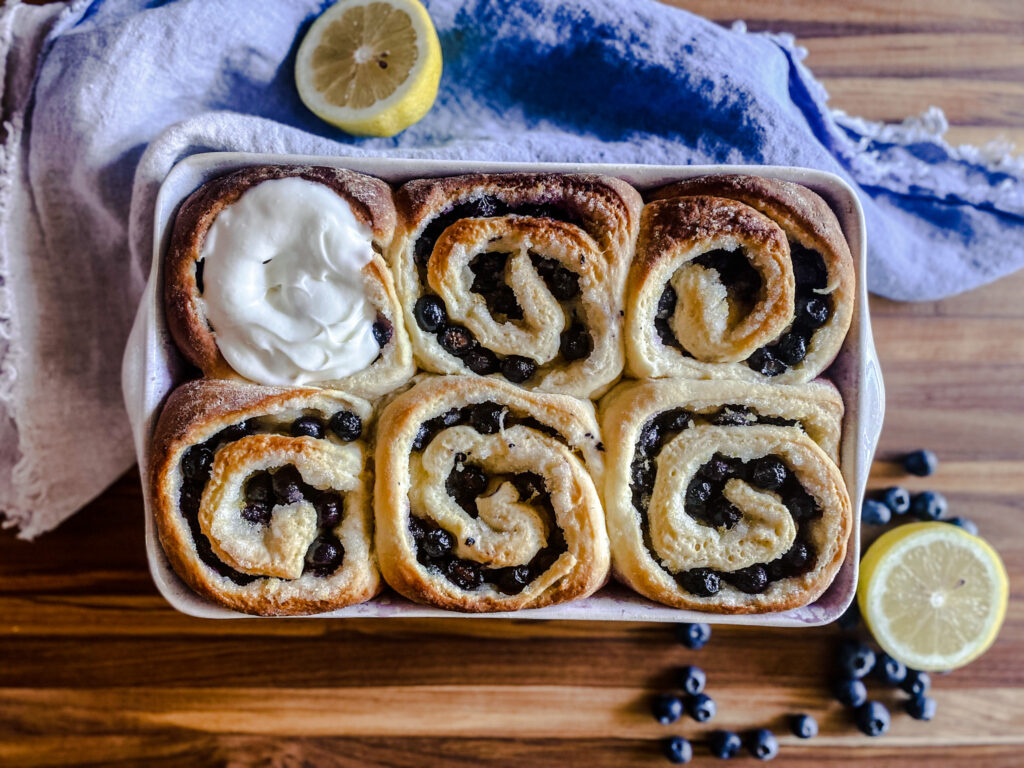 a pan of blueberry sweet rolls with lemons and blueberries and a napkin