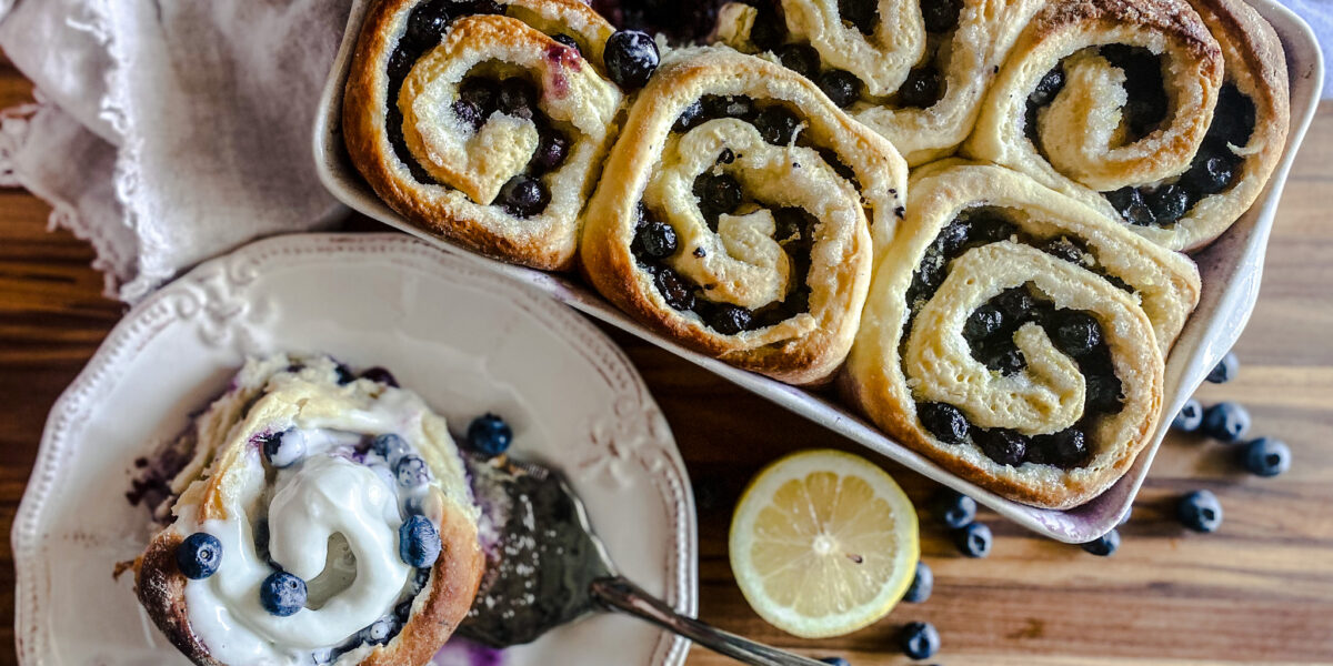 blueberry sweet rolls with one served on a plate with frosting and lemons and blueberries