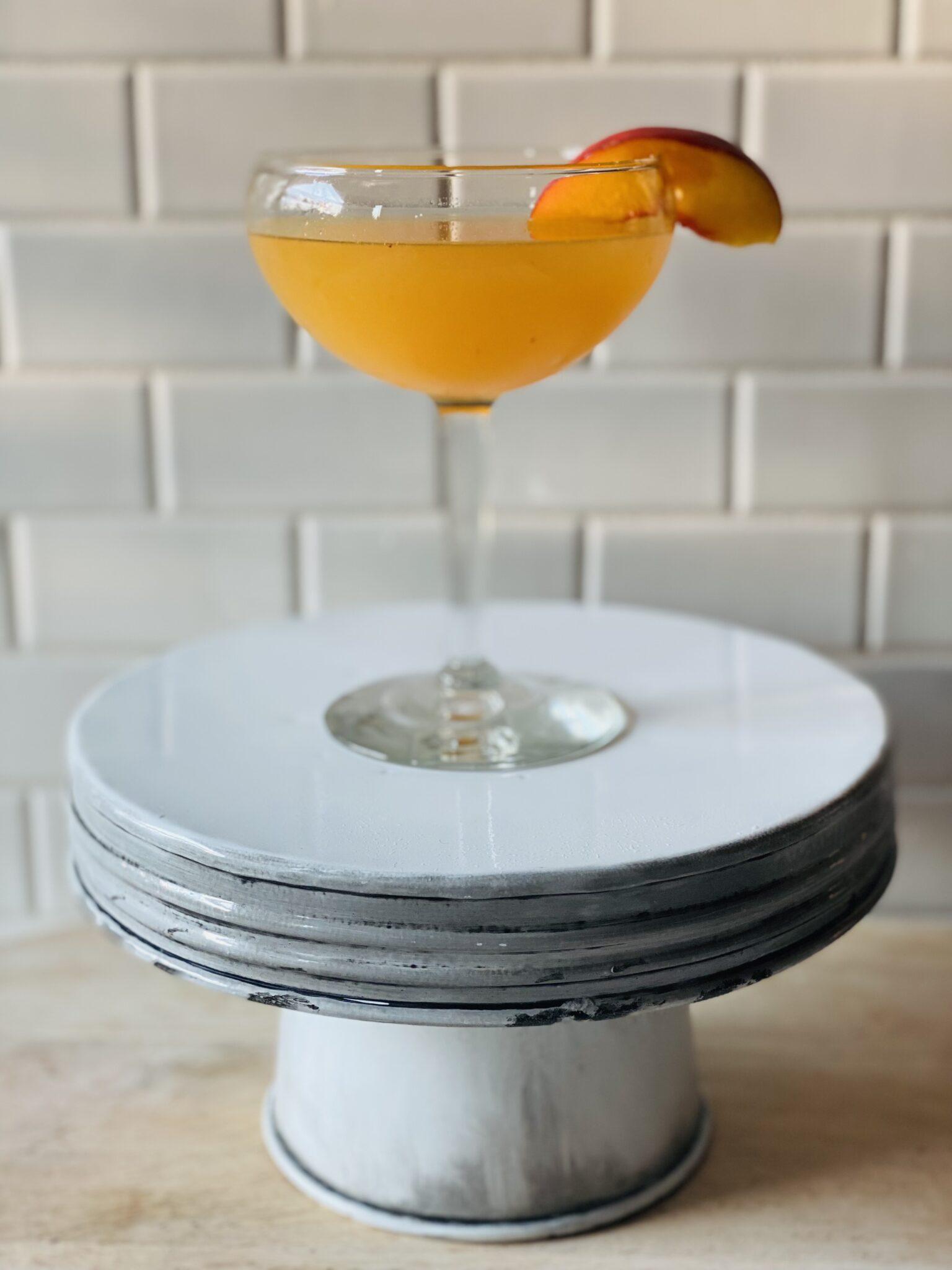 peach martini on a cake pedestal