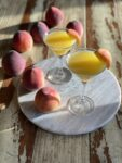 peach martinis on a marble round with peaches