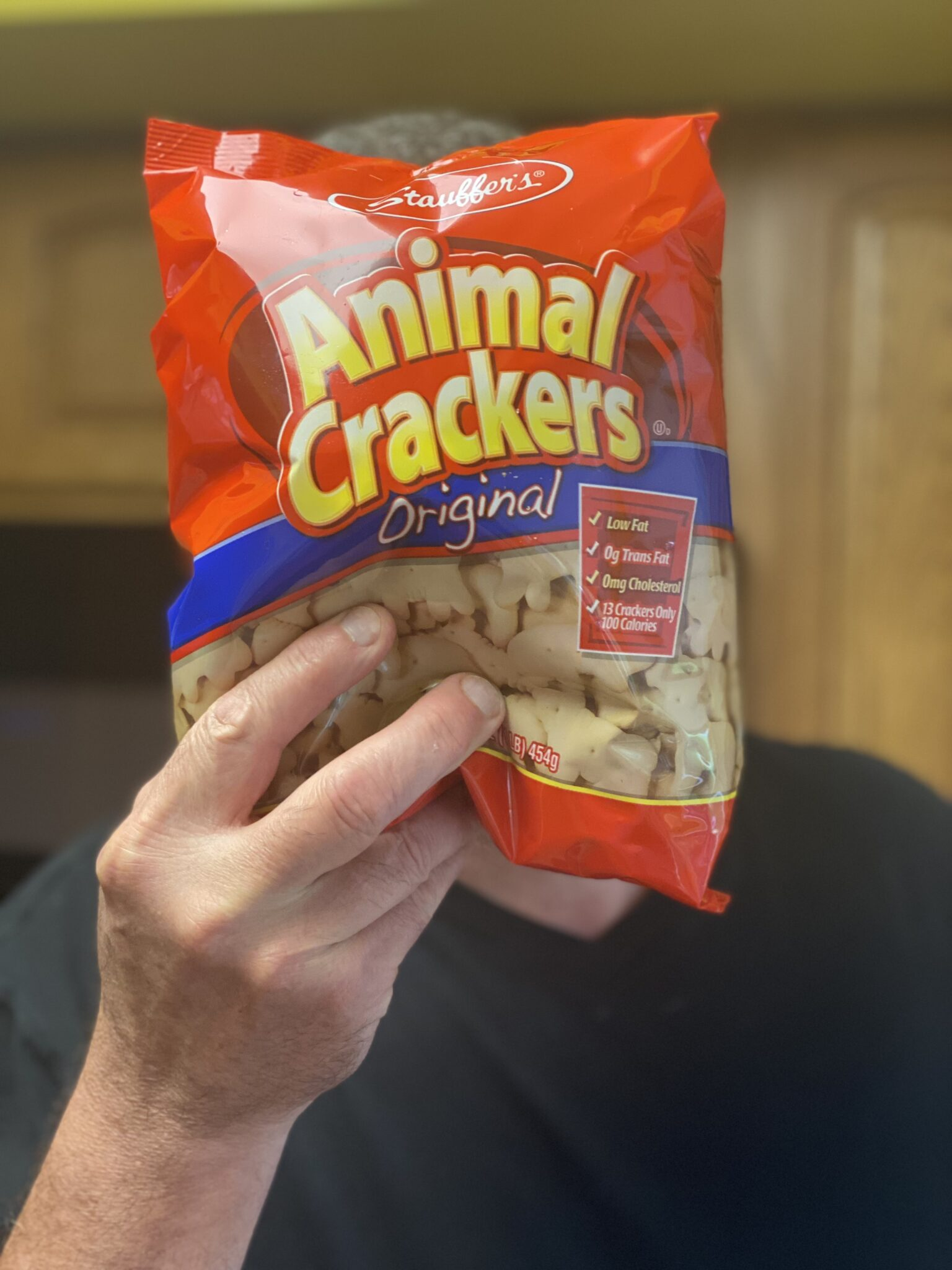 a hand holding a bag of animal crackers