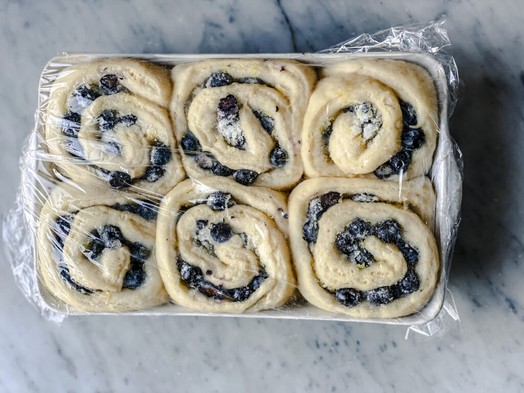 raised blueberry sweet rolls that have not been baked with plastic wrap