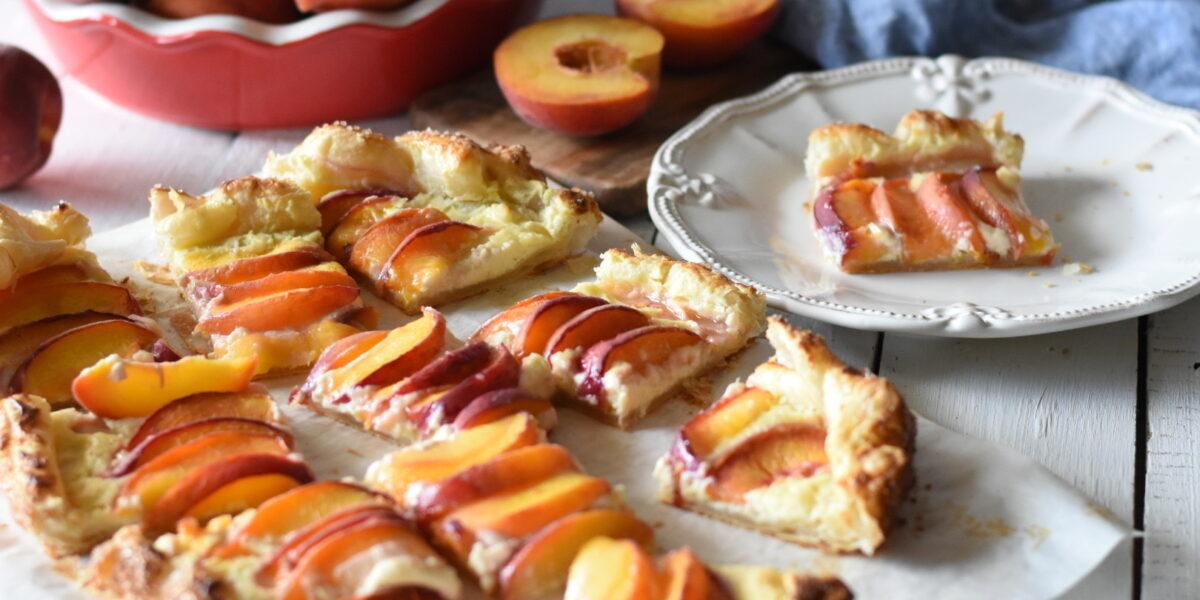 Fresh cream cheese peach galette cut into pieces with a bowl of peaches