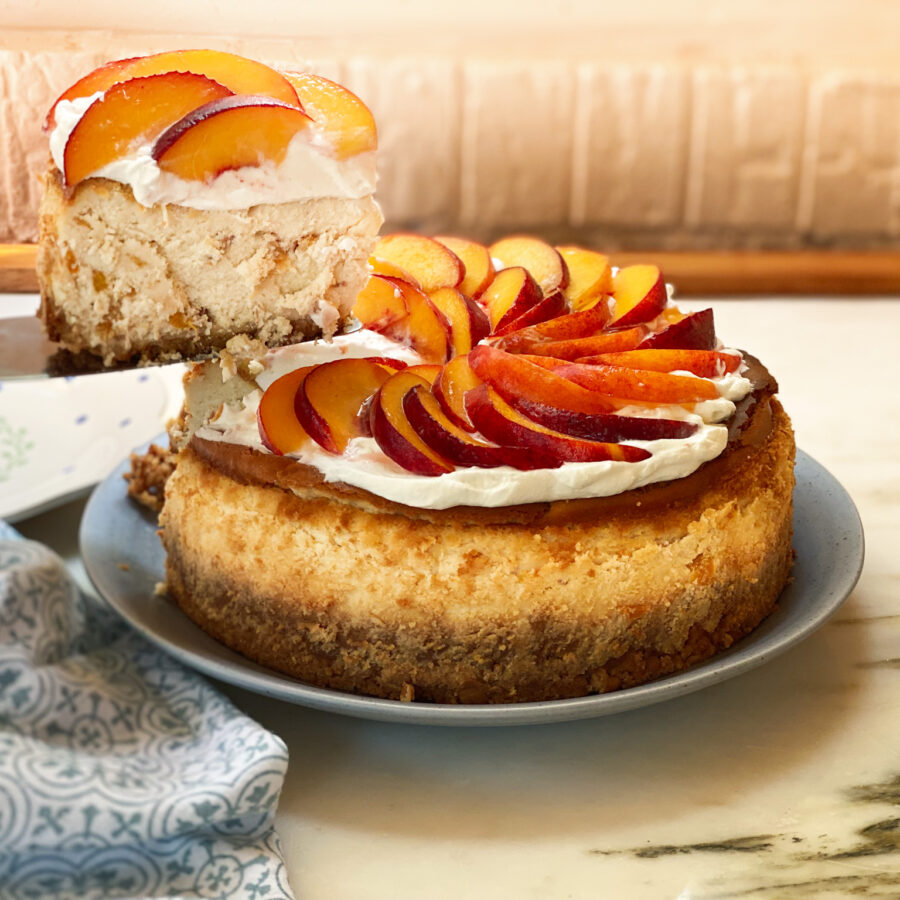 peach cheesecake with a slice out of it and a blue napkin