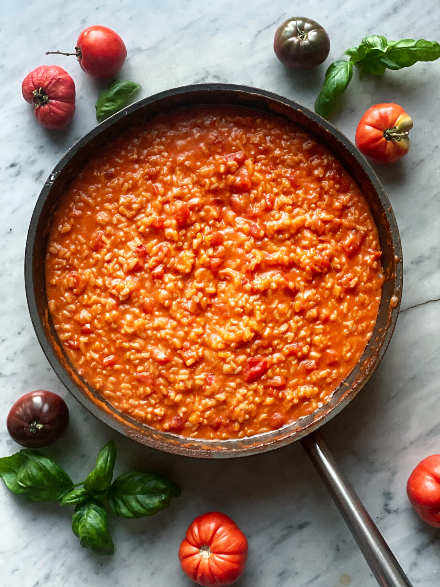 Tomato Risotto in pan with tomatoes around the pan