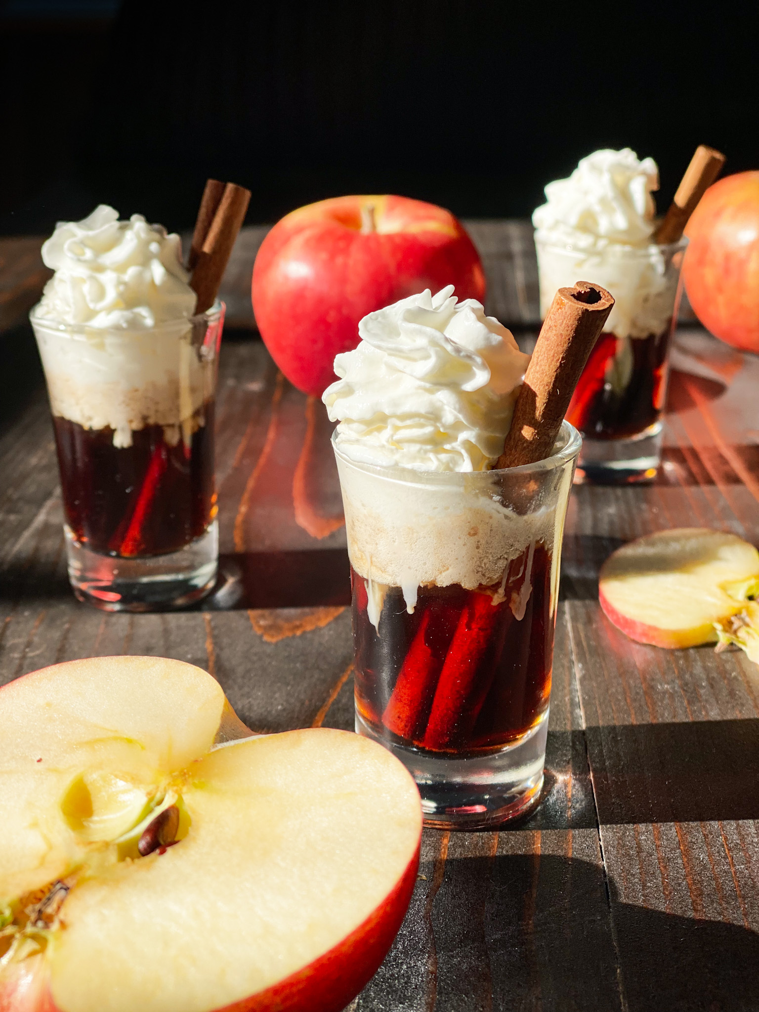 Apple Cinnamon Bourbon shots with whip cream and apples with one sliced