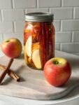 bourbon in a mason jar with apples and cinnamon sticks